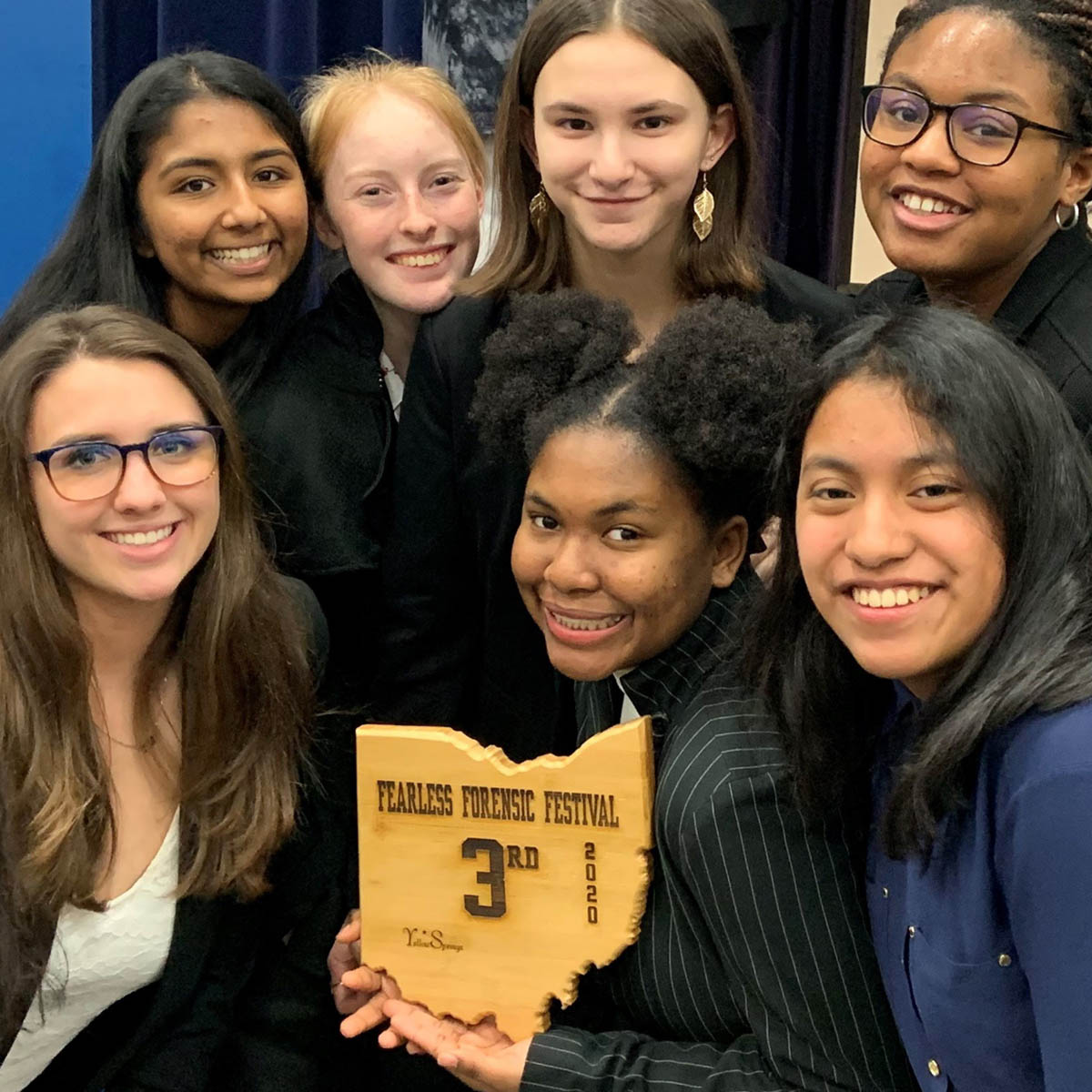 Stuednt posing and smiling with an award plaque.