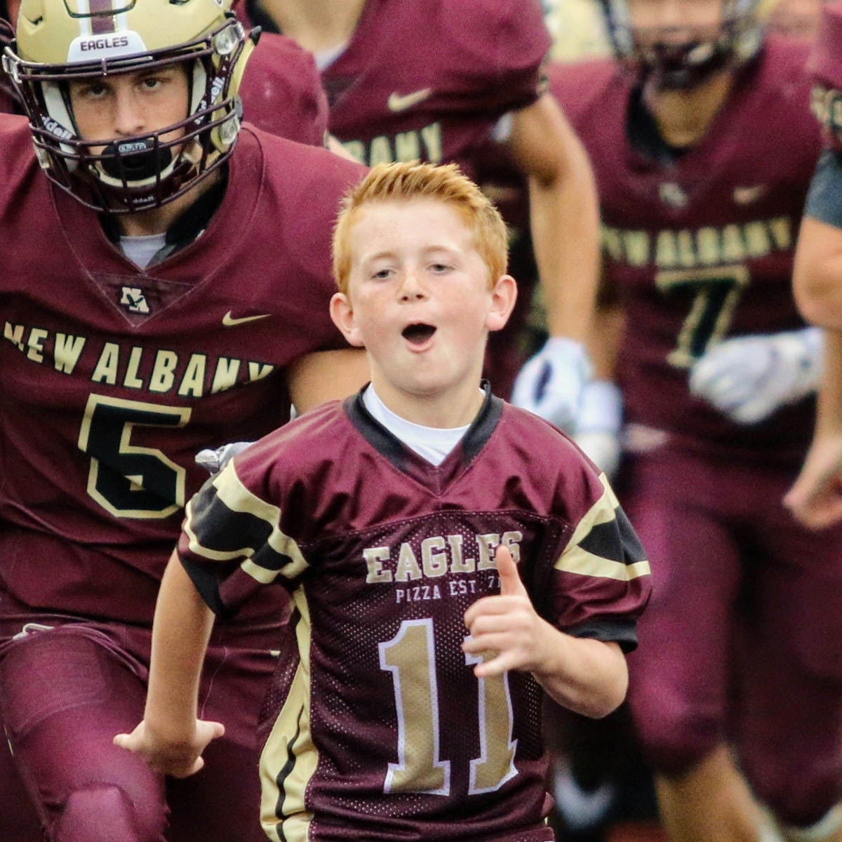 Young boy with a New Albany football jersey on running and cheering with the New Albany football team running behind him.