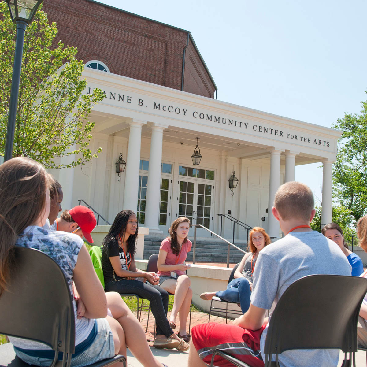 Students seated outside having a discussion.